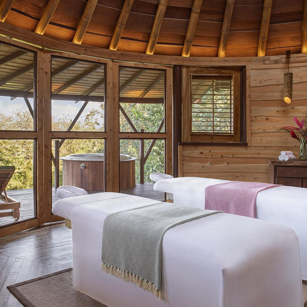 Origins Lodge, Bijagua - spa with two massage beds, rustic wooden structure, and doors leading to outdoor patio with jacuzzi
