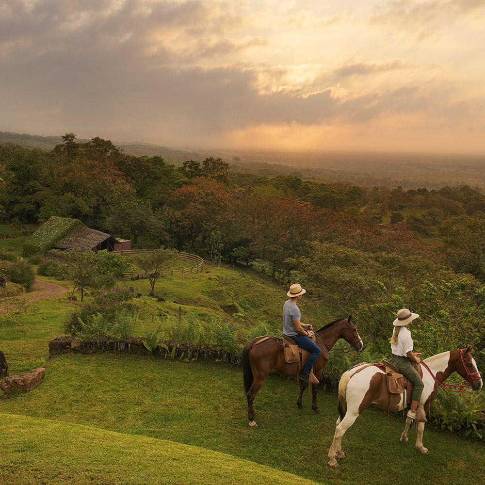Origins Lodge, Bijagua - man and woman riding horses in jungle landscape at sunset
