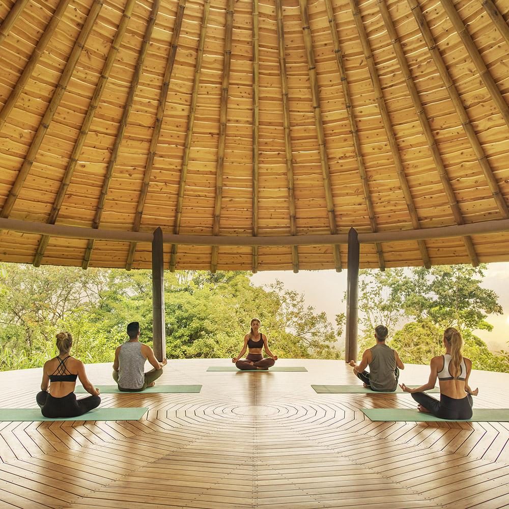 Origins Lodge, Bijagua - yoga class on a open air patio with a wooden roof overlooking jungle scenery