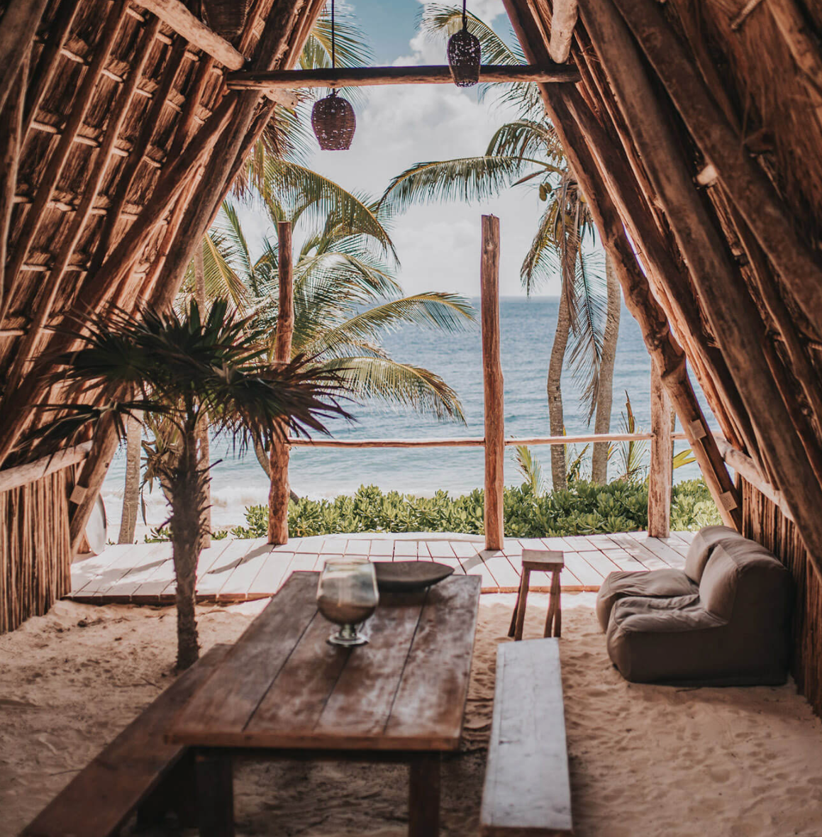 Papaya Playa Project, Tulum - jungle bungalow with thatch roof, bean bag lounges, and view of ocean