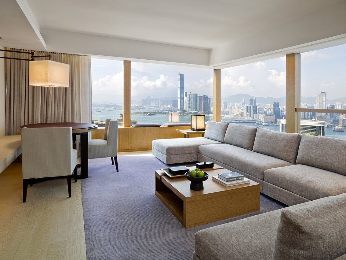 The Upper House, Hong Kong - hotel room with couch, dining table, chairs, coffee table with books, and windows overlooking Victoria Harbour