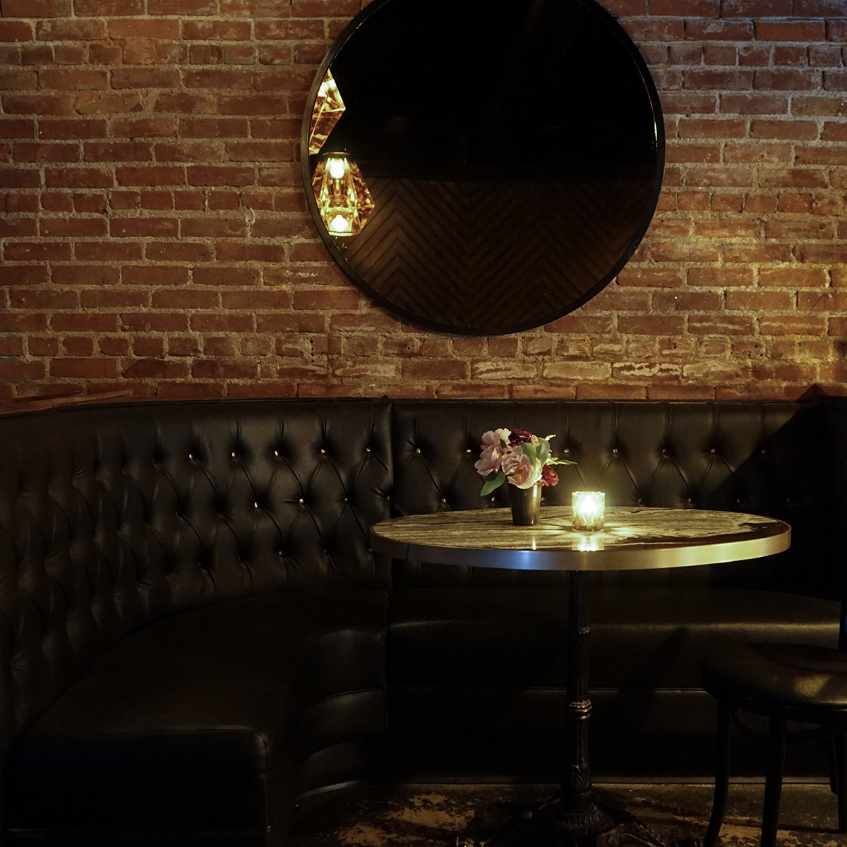 Gold-Diggers, Los Angeles - hotel lounge with black leather couch, round metal table, brick walls, and large round wall mirror