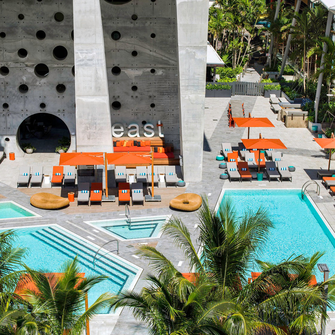 EAST, Miami - hotel outdoor space with four different pools, orange and grey lounge chairs, sun umbrellas, and palm trees