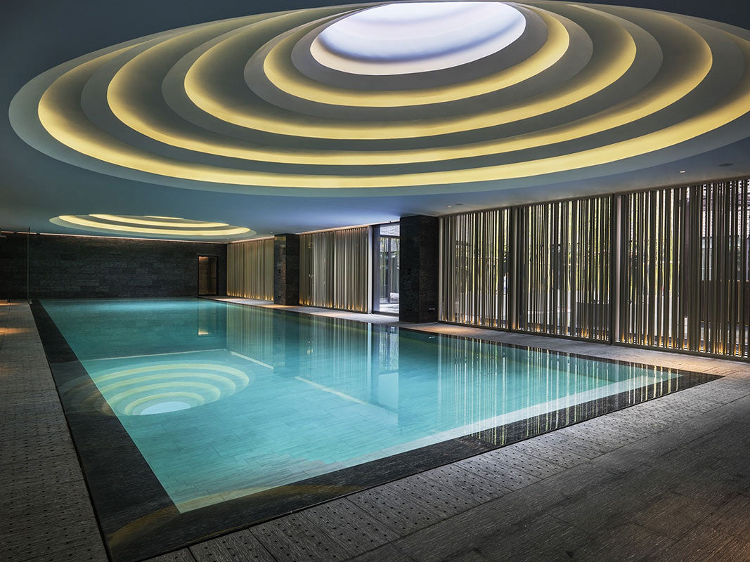 The Temple House, Chengdu - hotel pool with dark stone floor and intricate skylight and circular light ceiling