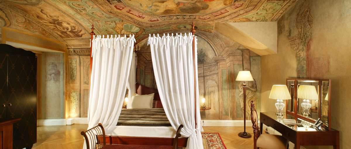Smetana Hotel, Prague - hotel room with curtained canopy bed, fresco style walls and ceiling, and antique mirror vanity