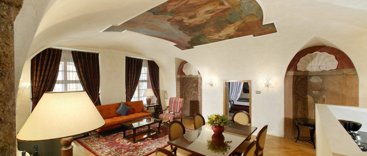 Smetana Hotel, Prague - hotel living room with antique dining table, chairs, couch, and fresco wall designs