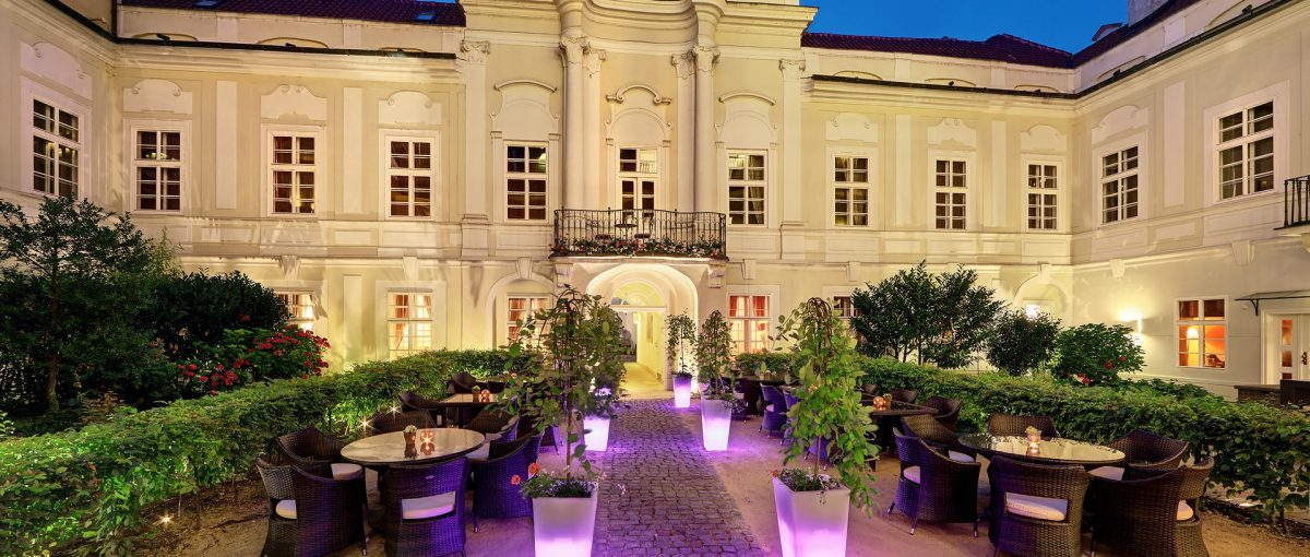 Smetana Hotel, Prague - hotel courtyard with historic European building, tables, wicker chairs, and manicured garden at night