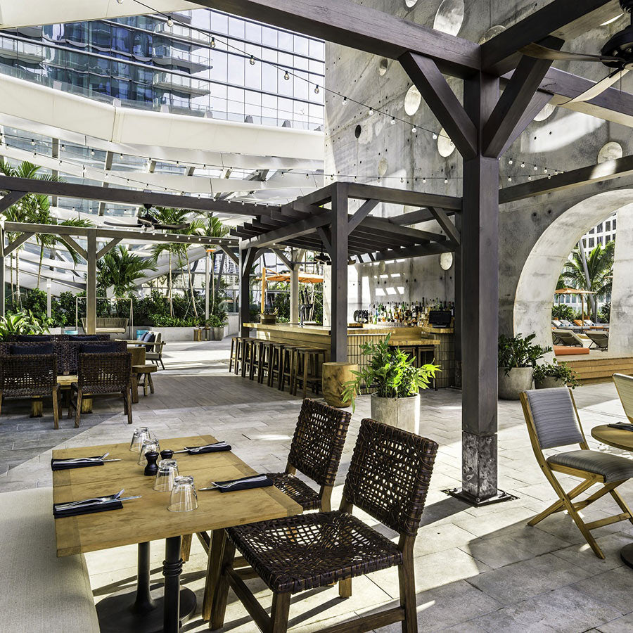 EAST, Miami - rooftop restaurant with set tables, a bar, and wooden sun shade structures