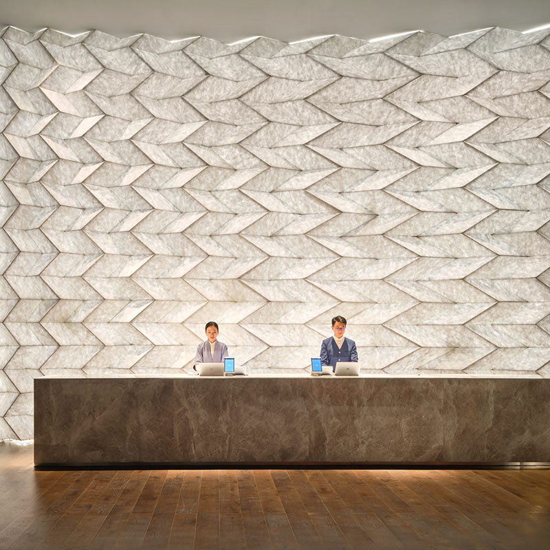 The Opposite House, Beijing - hotel stone reception desk with two employees behind desk and a white 3D design wall