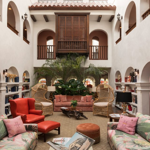 Casa Faena, Miami Beach - hotel lobby with armchairs, couches, bookshelves, and a balcony on the second floor