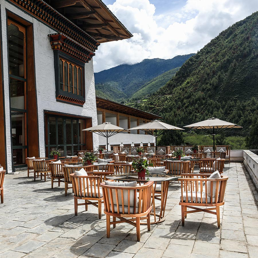 Bhutan Spirit Sanctuary, Bhutan - outdoor dining patio with chairs, tables, and sun umbrellas and a mountain view