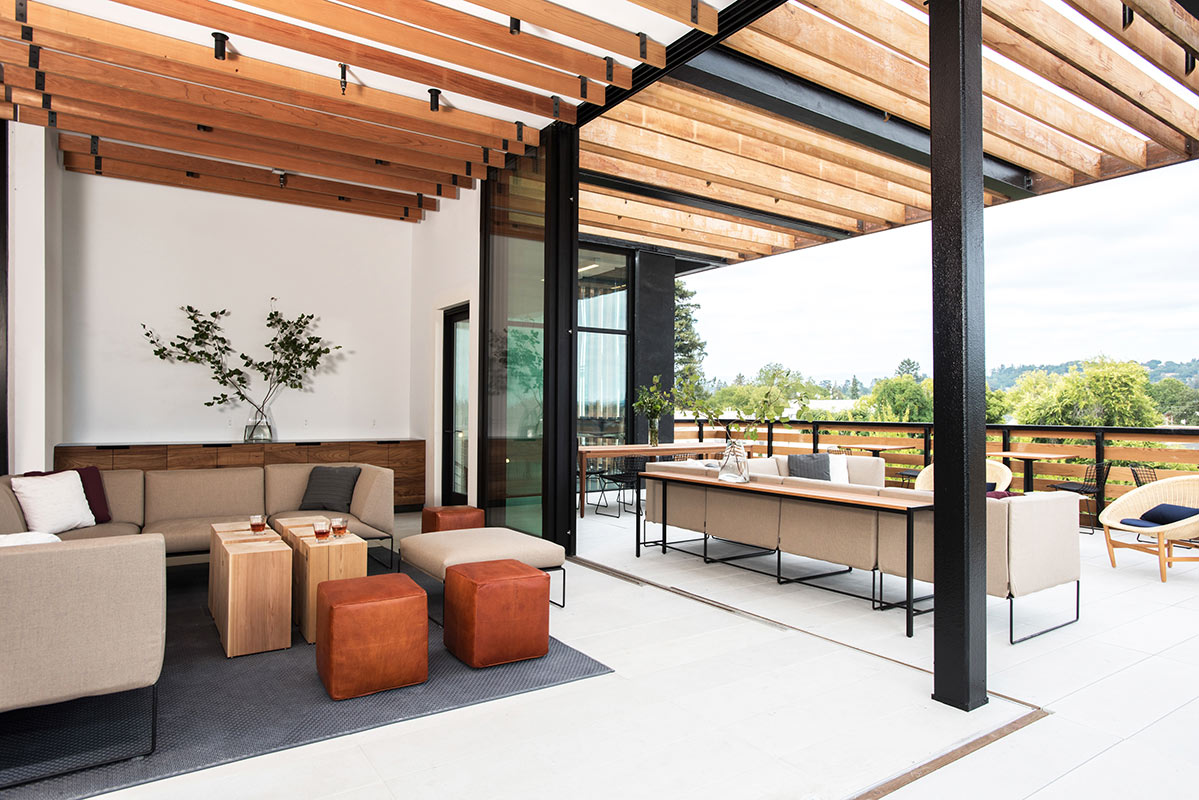 Harmon Guest House, Healdsburg - hotel lounge with sofa, floor to ceiling glass doors, patio, and forest view