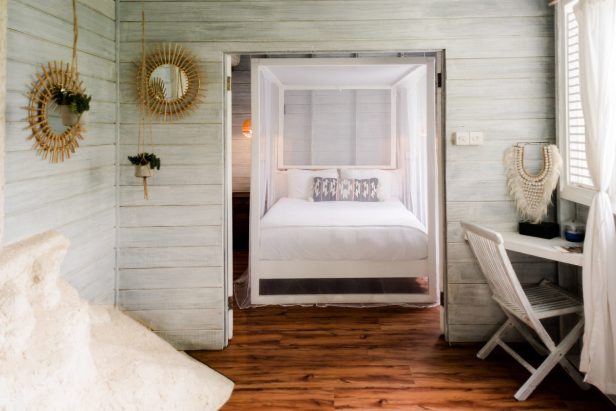ECO Lifestyle + Lodge, Barbados - Hotel room with white wood walls, local island decorations, and four poster bed