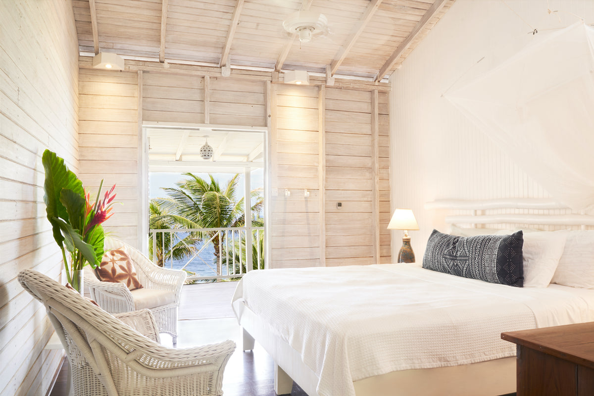 ECO Lifestyle + Lodge, Barbados - hotel room with white wood walls, white wicker chairs, bed, and balcony overlooking ocean