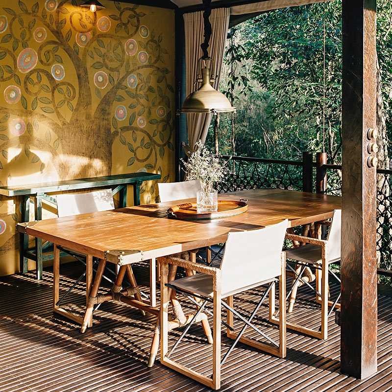 Shinta Mani Wild, Kirirom National Park - open air patio with dining table and chairs with an intricate golden tree mural behind the table