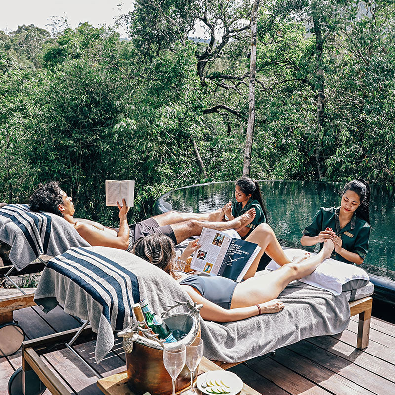 Shinta Mani Wild, Kirirom National Park - man and woman on lounge chairs while two women massage their feet in jungle resort setting