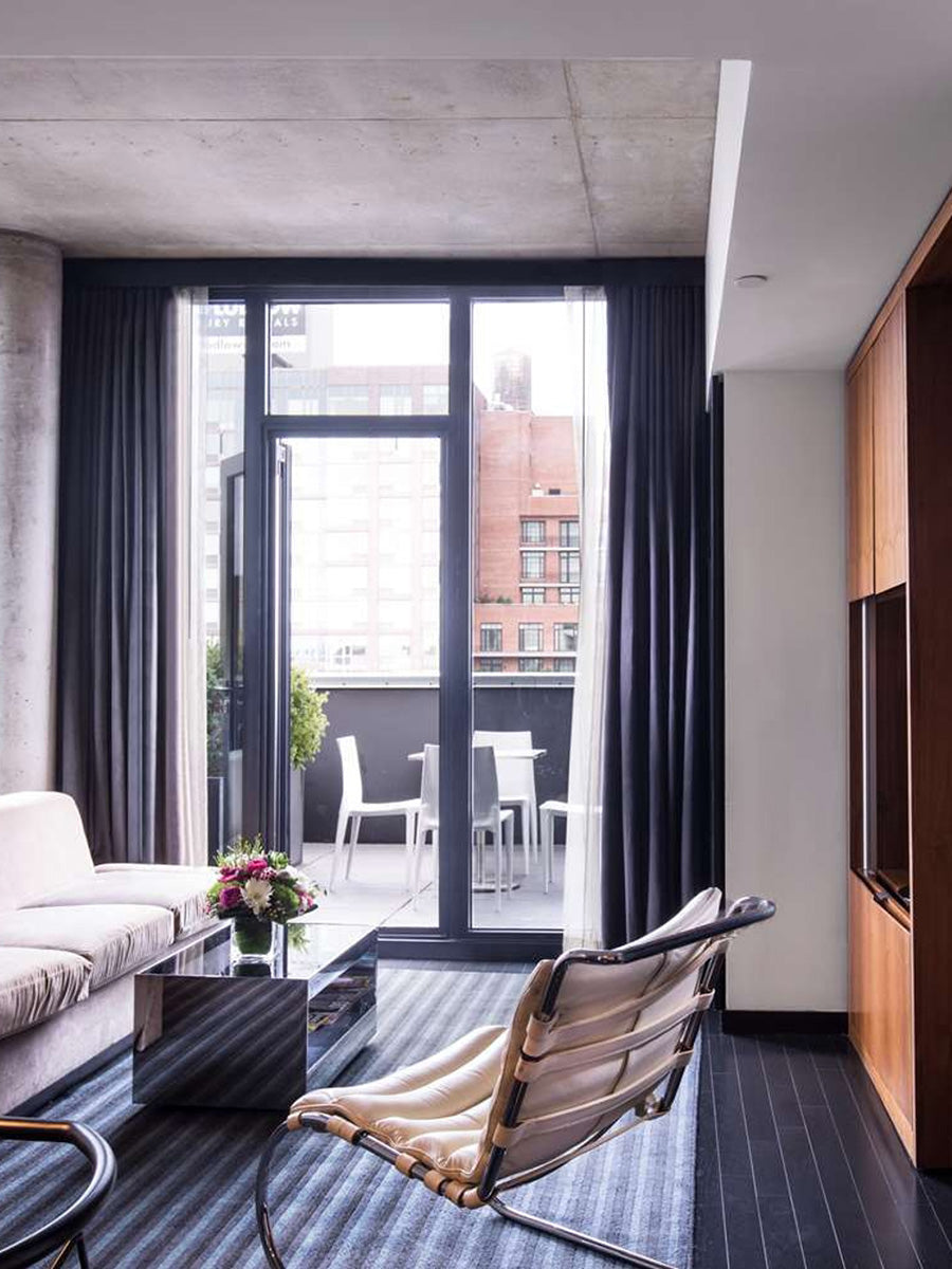 Sixty LES, NYC - hotel room with grey striped carpet, white furniture, and floor to ceiling windows leading to private balcony