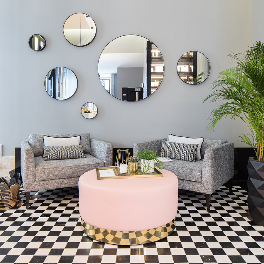 The Lumiares, Lisbon - hotel lobby with hanging circular mirrors, grey armchairs, pink coffee table, and checkered tile floor