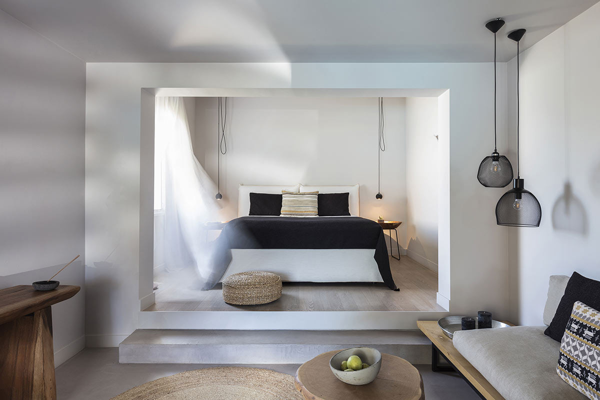 Minos Beach Art Hotel, Crete - contemporary hotel room with black and white theme and stairs leading from living room to bed