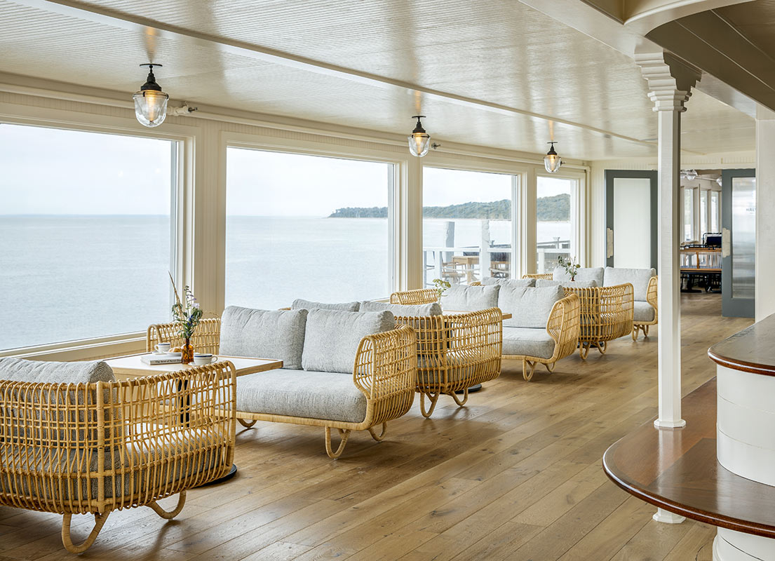 Sound View, Greenport - nautical hotel lounge with ocean view windows and rows of wicker couches