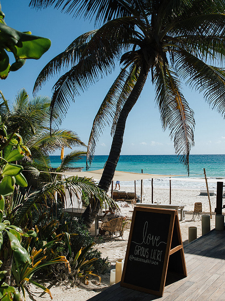 "Sanará, Tulum - resort patio with chalkboard sign ""Love grows here"" overlooking white sand beach and ocean"