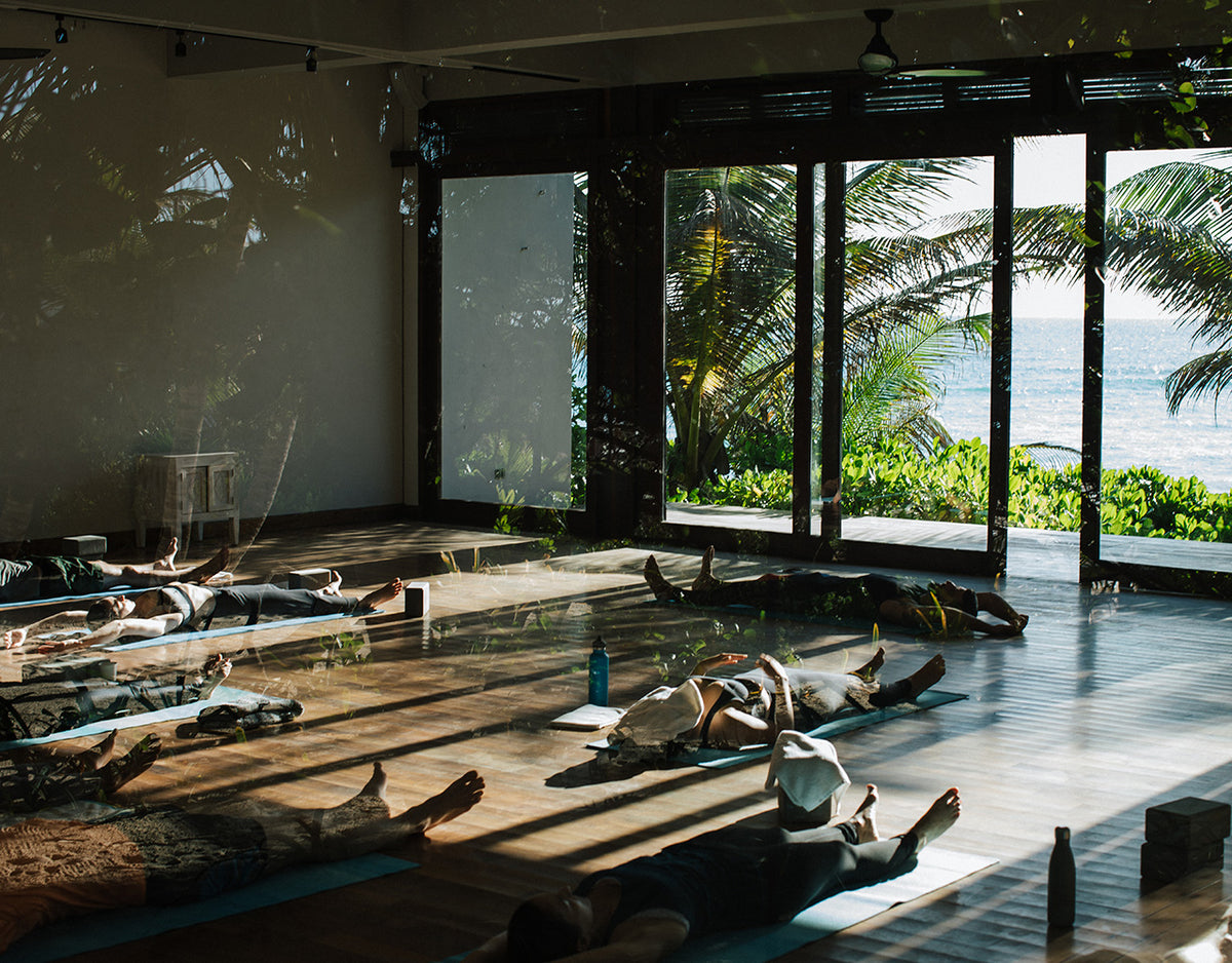 Sanará, Tulum - yoga class with people laying on their backs in a small room with sliding door windows leading to a patio and ocean view