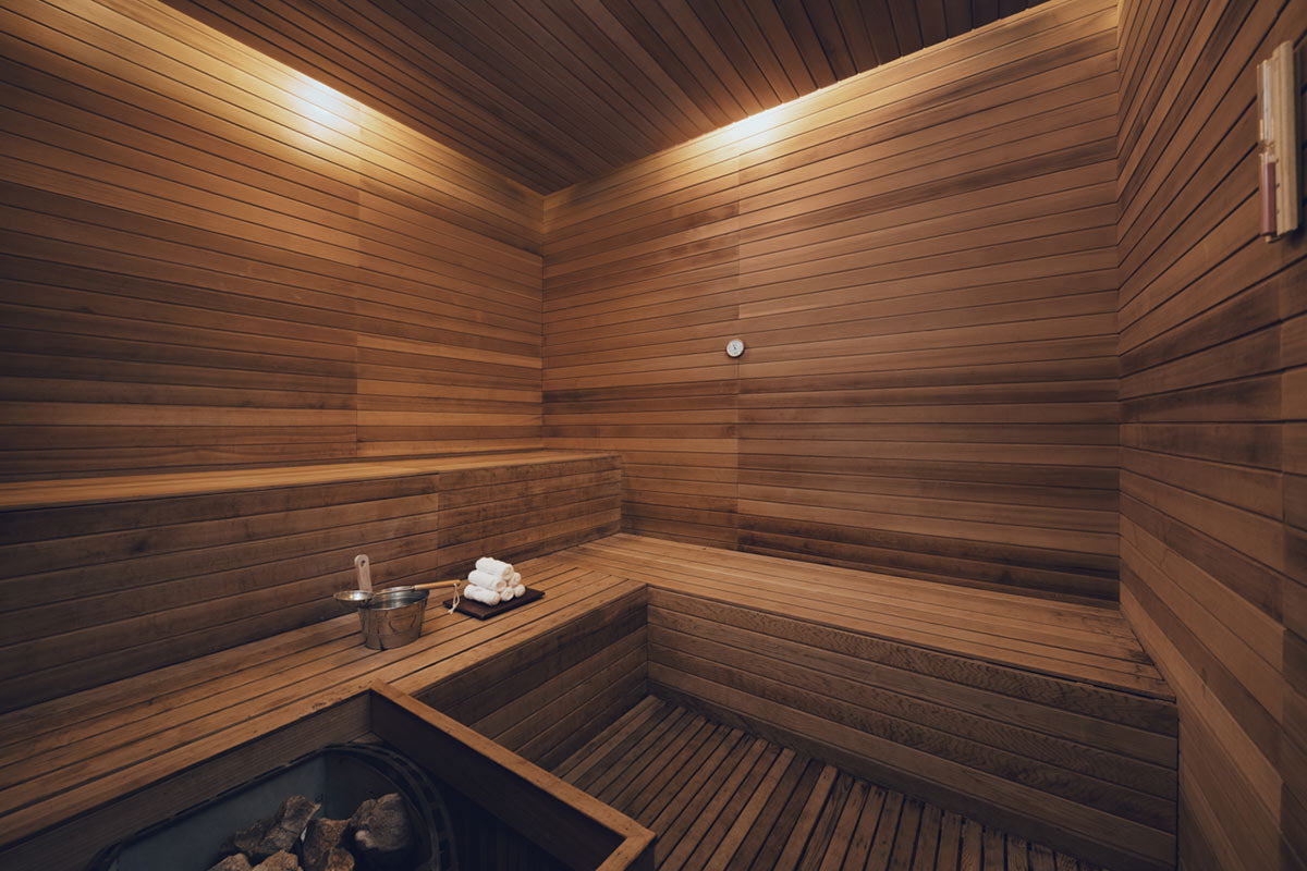 The Temple House, Chengdu - wood sauna with rolled towels, water bucket, and steam fireplace