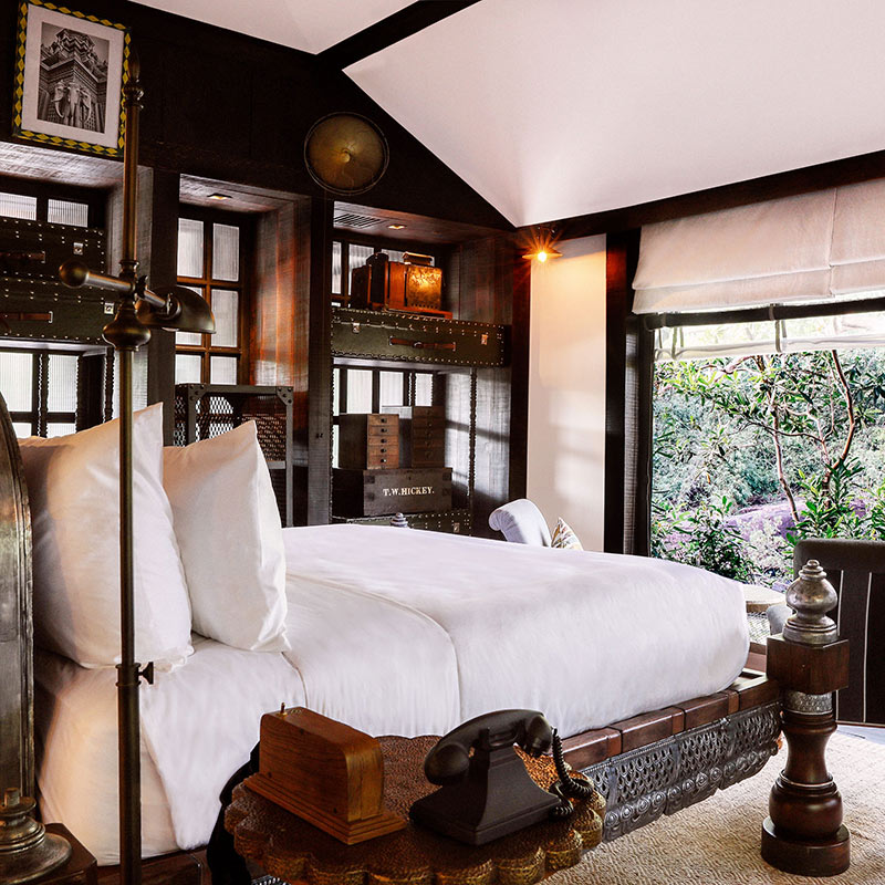 Shinta Mani Wild, Kirirom National Park - vintage style dark wood hotel room with white bed and a large window overlooking jungle