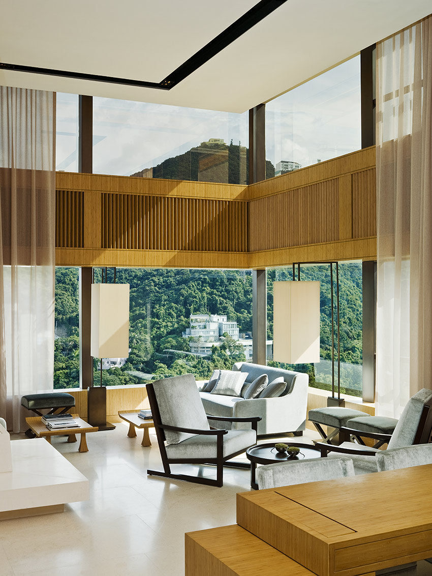 The Upper House, Hong Kong - hotel room with tall ceilings, couch, armchairs, and windows overlooking mountain