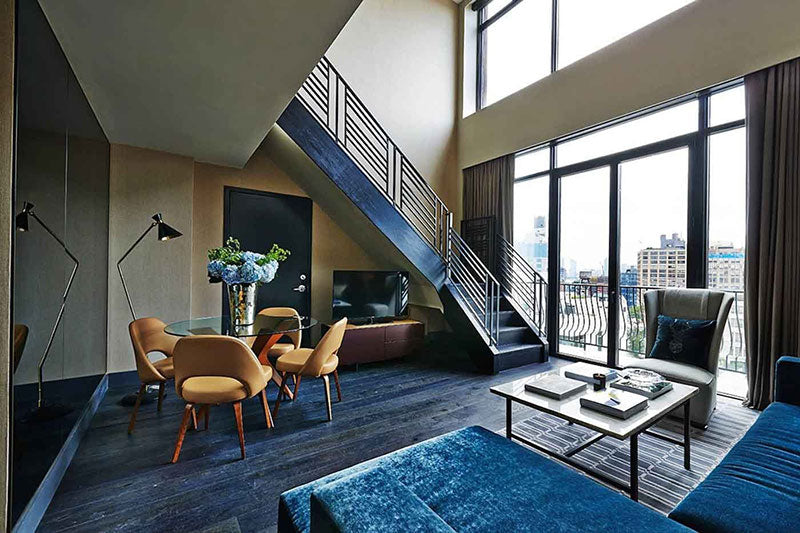 Sixty Soho, NYC - hotel room with blue velvet couch, gold chairs, staircase, and windows overlooking city