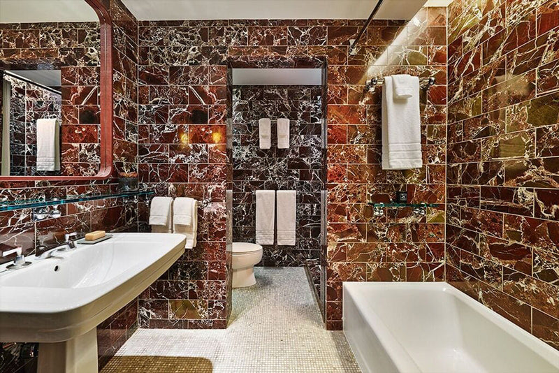 Sixty Soho, NYC - hotel bathroom with large white sink, white dub, and red stone tile walls