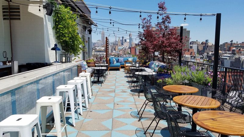 Sixty Soho, NYC - rooftop bar with white metal stools, metal chairs, wooden tables, teal couches, and string lights overlooking city