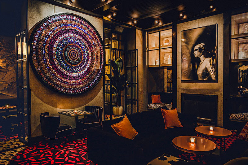 Sixty Soho, NYC - Butterfly bar interior with dark couches, chairs, and tables, and unique colorful art on the walls