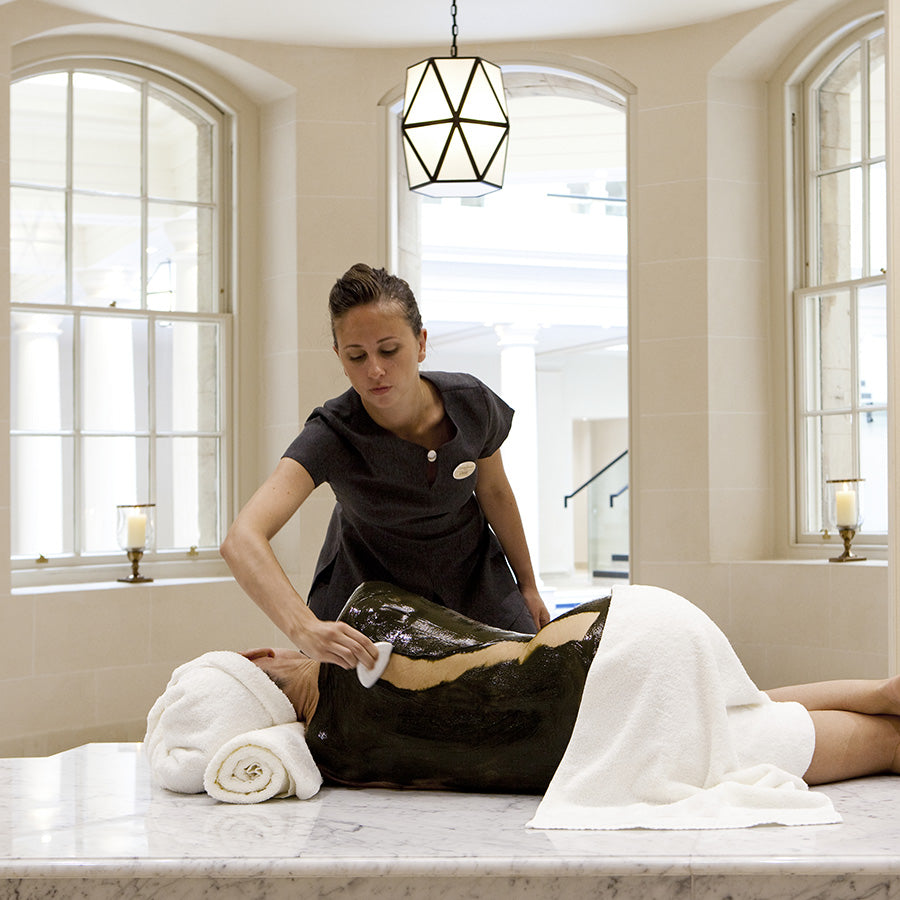 The Gainsborough Bath Spa, Bath - woman laying on a massage table with a black mask treatment while a woman wipes the mask away
