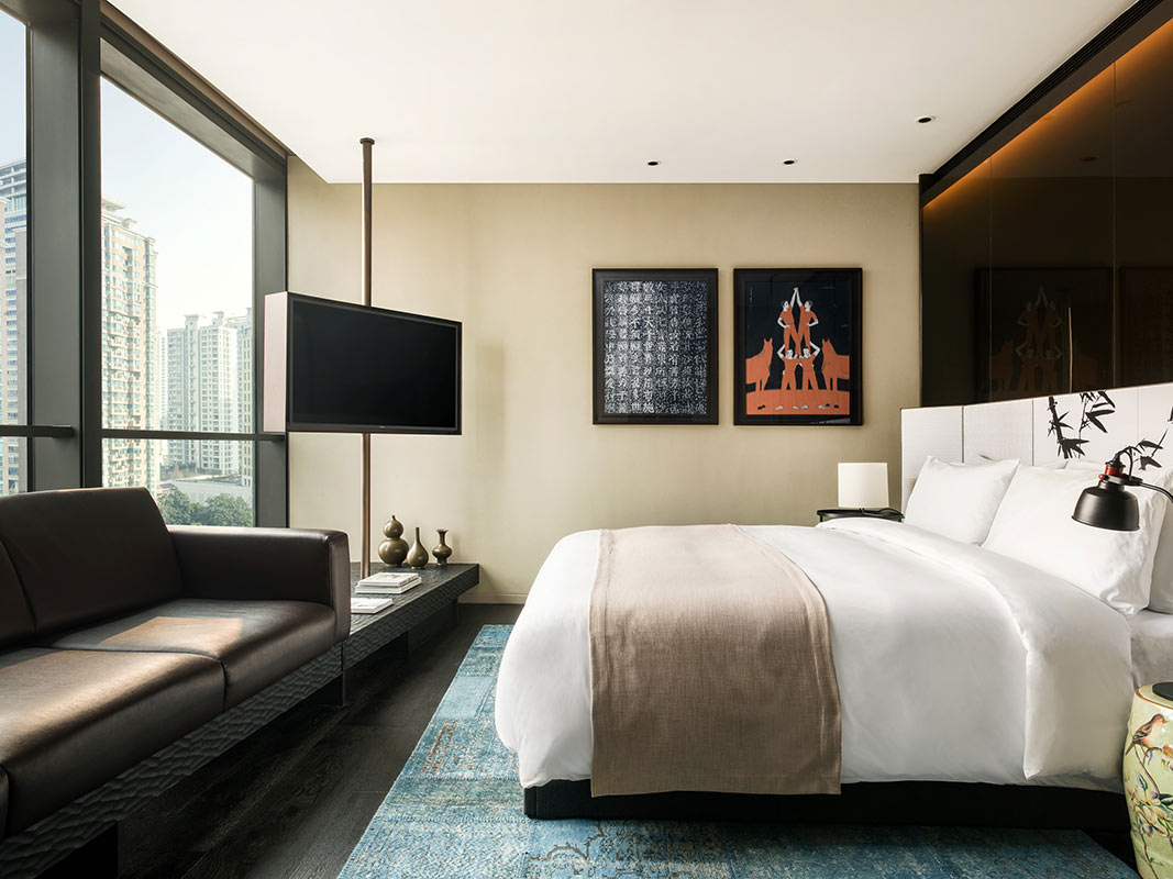 The Middle House, Shanghai- hotel room with bed, couch, tv, and window overlooking city