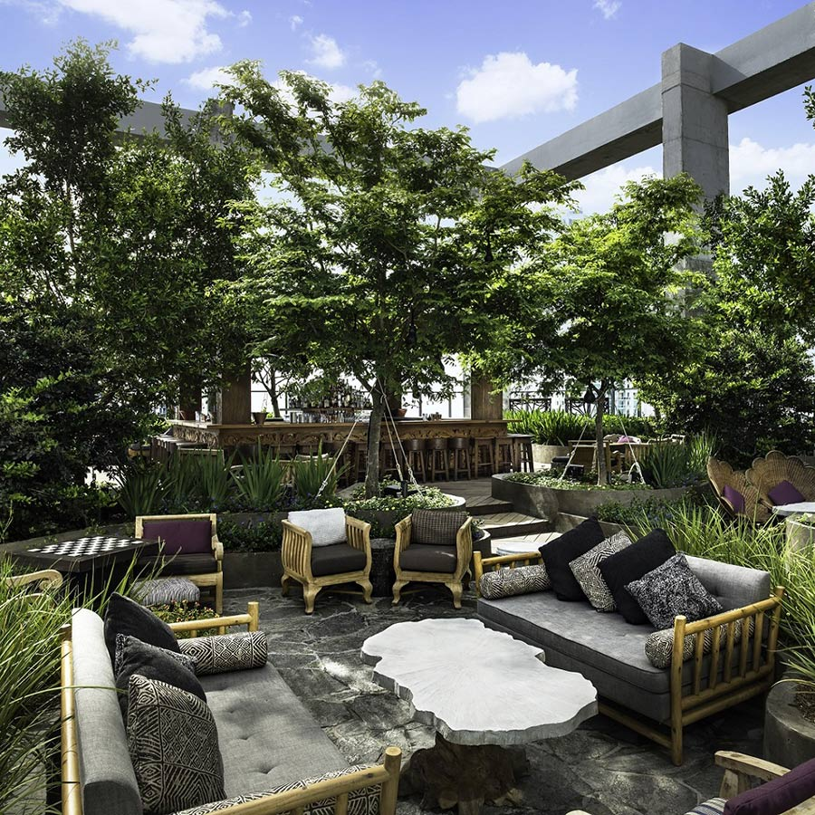 EAST, Miami - rooftop green space with chairs, couches, and coffee tables