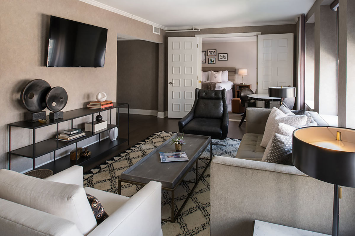 Claridge House, Chicago - hotel living room with beige couches, wooden coffee table, and mounted tv