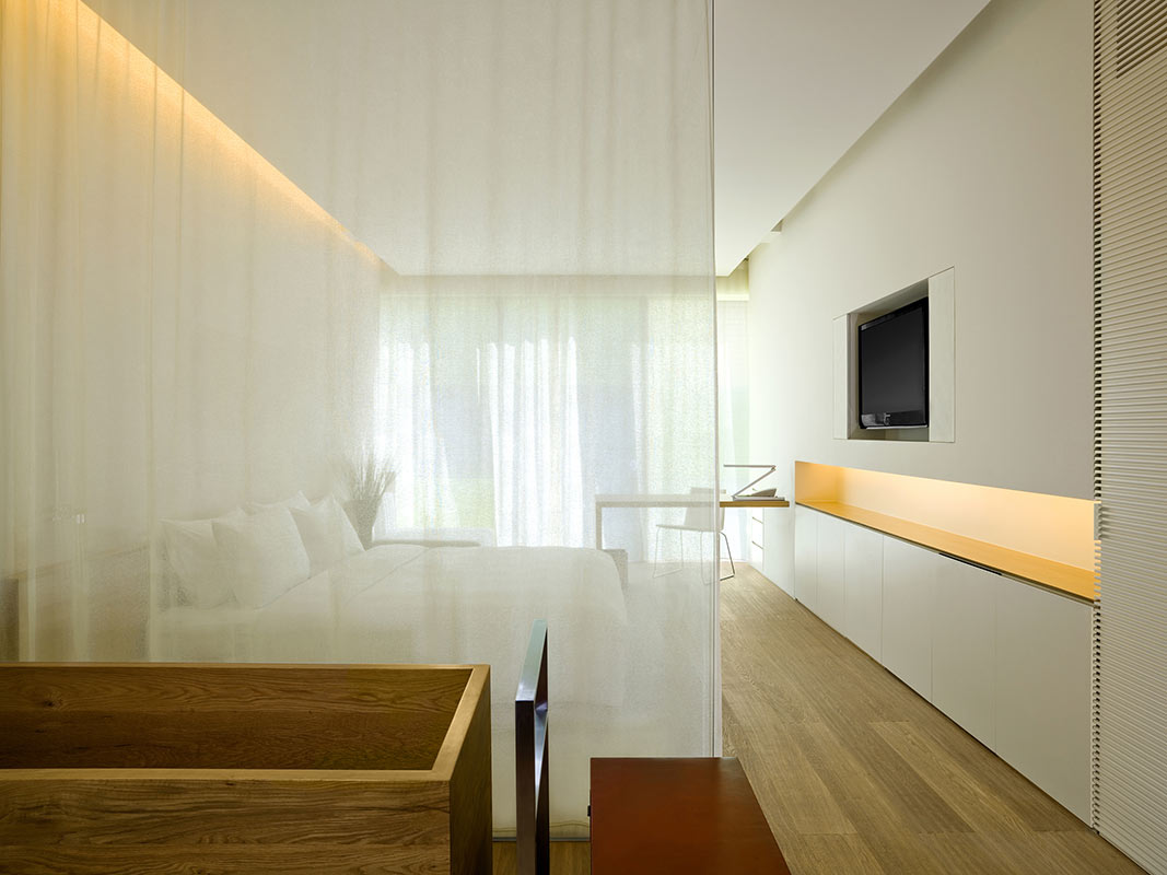 The Opposite House, Beijing - hotel room with a sheer curtain separating the bed from another area