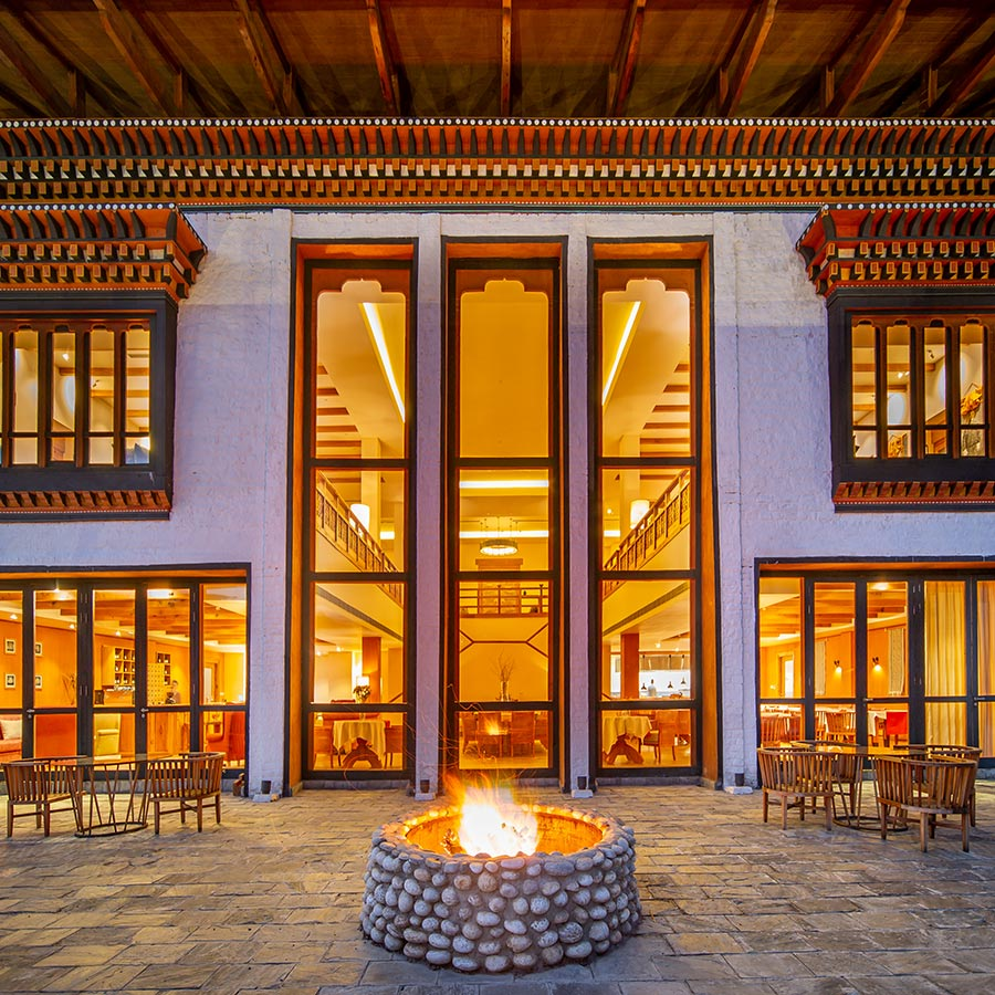 Bhutan Spirit Sanctuary, Bhutan - exterior of hotel lobby with stone patio, wooden furniture, fire pit, and large ornate windows