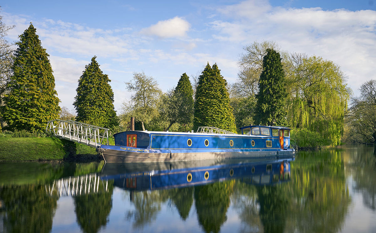 Monkey Island Estate, The Thames- docked blue river boat with tall evergreen trees and willow trees lining the river