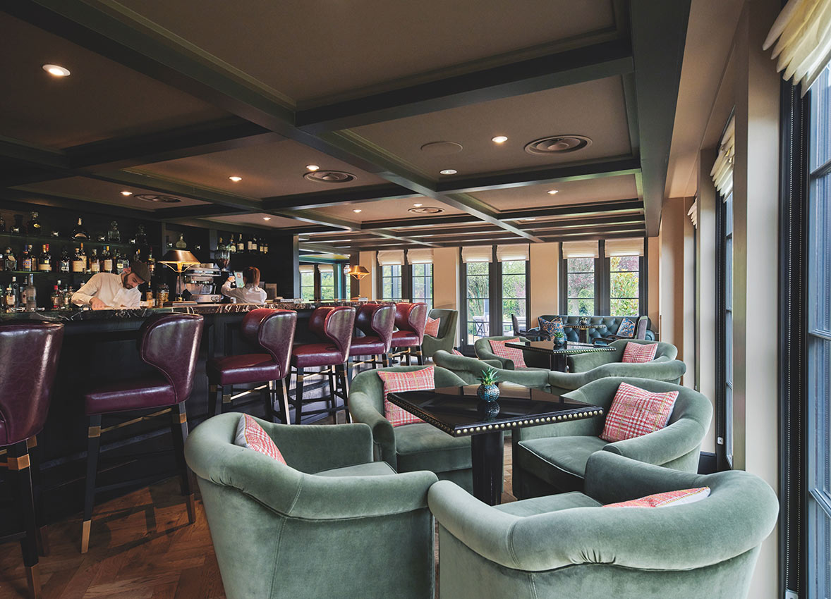 Monkey Island Estate, The Thames-  hotel bar with bartenders making drinks, purple leather barstools, and sage velvet armchairs