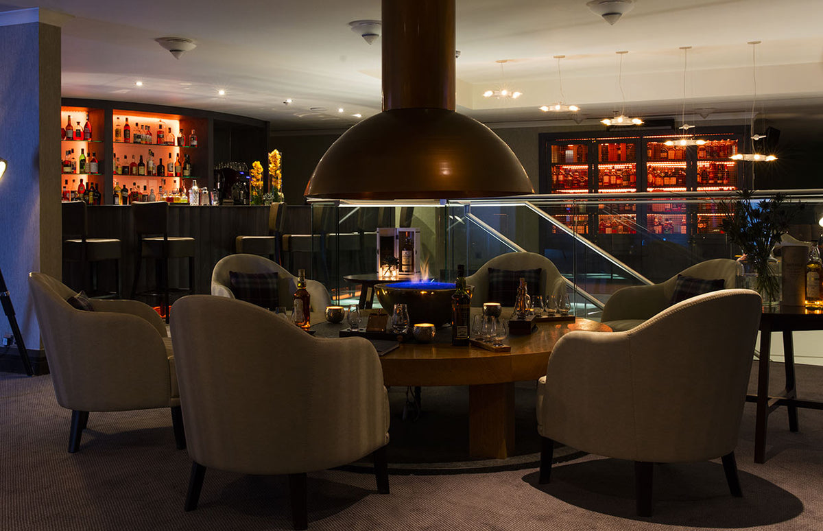 The Glasshouse, Edinburgh - The Snug bar with armchairs around a round table and bar in background
