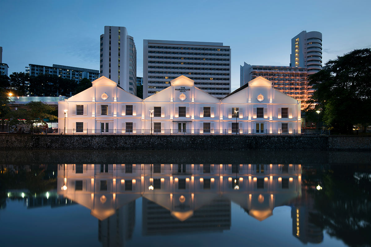 The Warehouse Hotel, Singapore - hotel exterior lit up at night, 3 triangular warehouse facades reflected in a pond