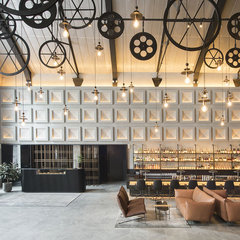 The Warehouse Hotel, Singapore - hotel lobby with bar, couches, reception desk, and hanging gear decorations
