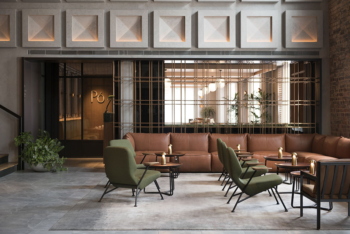 The Warehouse Hotel, Singapore - hotel lounge with tables, chairs, and brown leather couch outside of restaurant Po