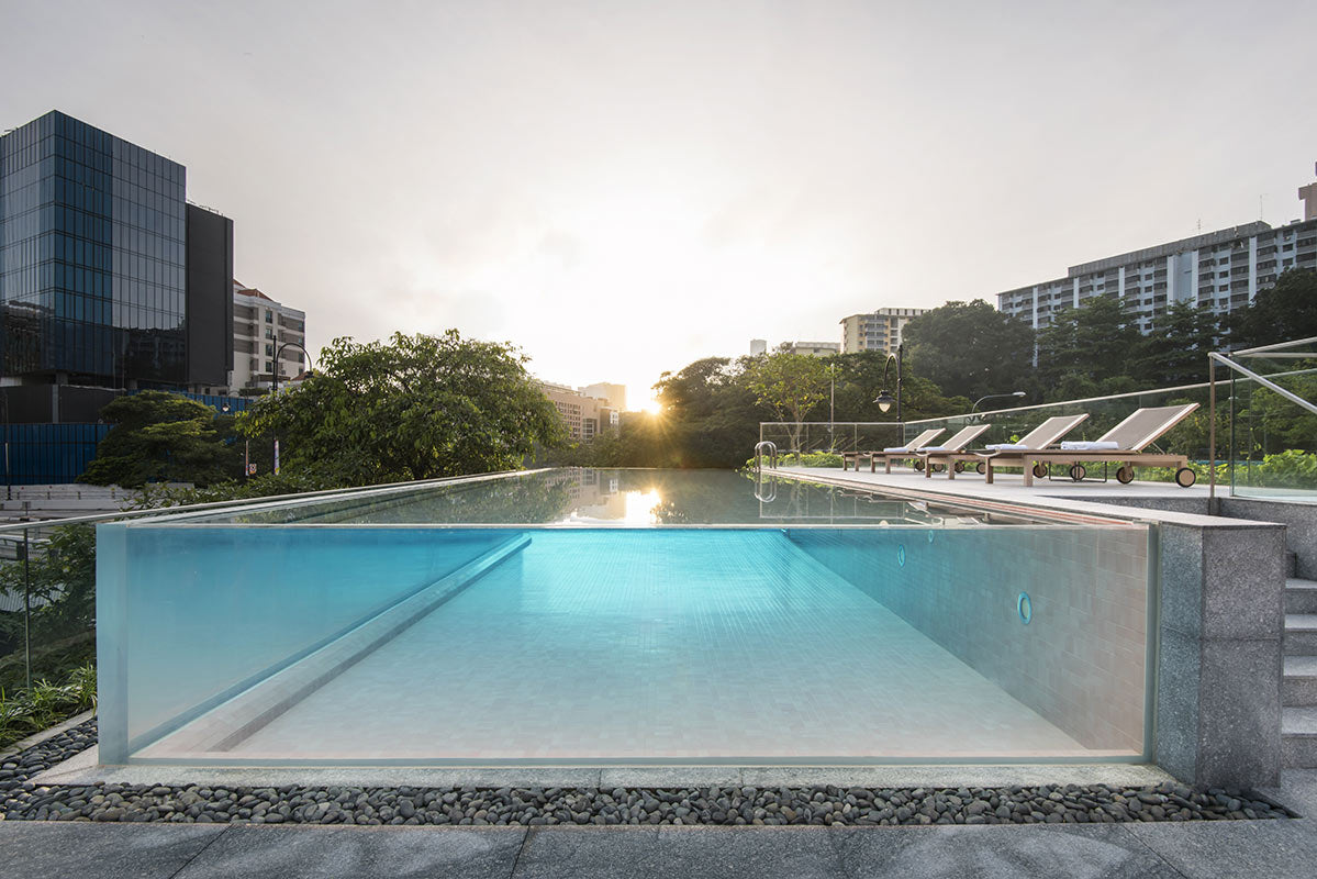 The Warehouse Hotel, Singapore - outdoor hotel pool with glass walls, lounge chairs, and city view
