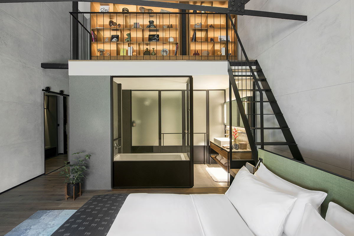 The Warehouse Hotel, Singapore - hotel room with bed, bathroom, bathtub, and stairs leading to loft area