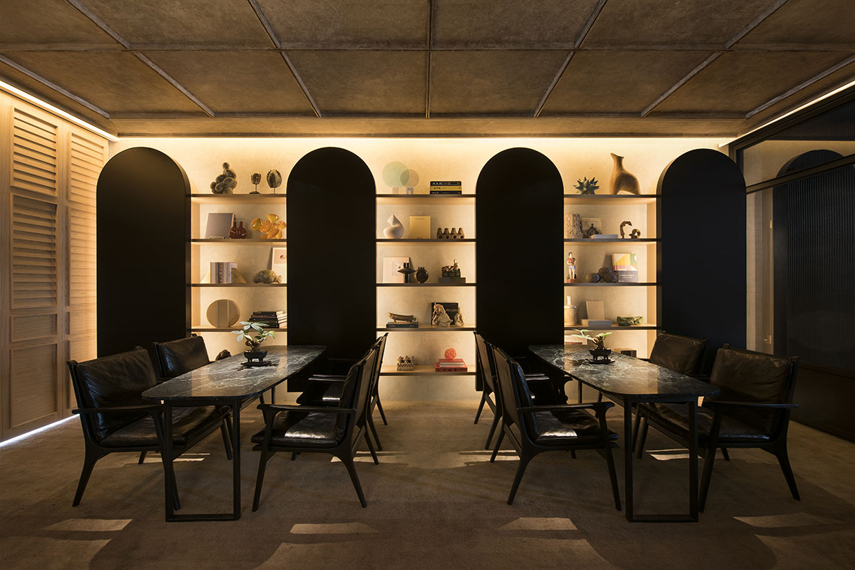 The Warehouse Hotel, Singapore - The Den tables with lit bookshelf decorations