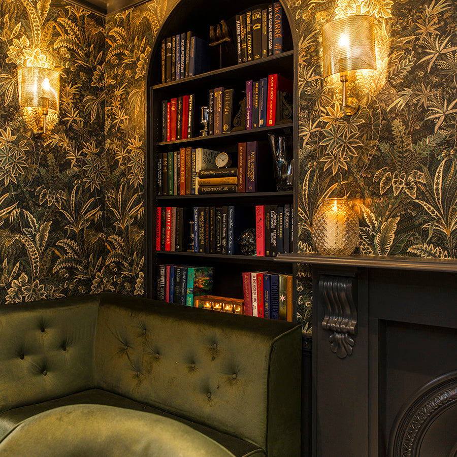 The Academy Hotel, London - hotel lounge with decorative golden plant wall paper, green velvet couch, and library wall bookshelf