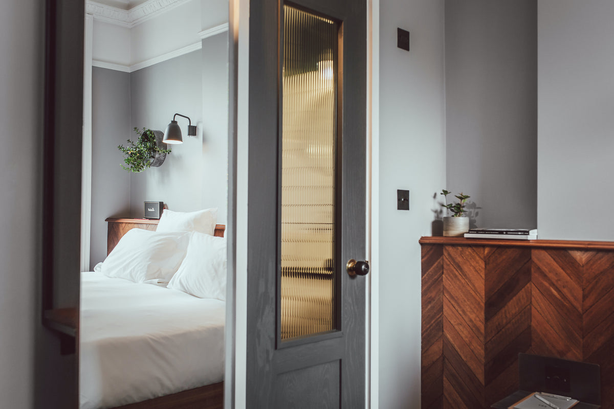 The Pilgrm, London, UK - hotel room with grey wood door leading to bed